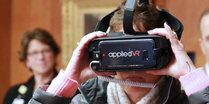 Peggy O'Neil Verronneau tries on applied VR device
