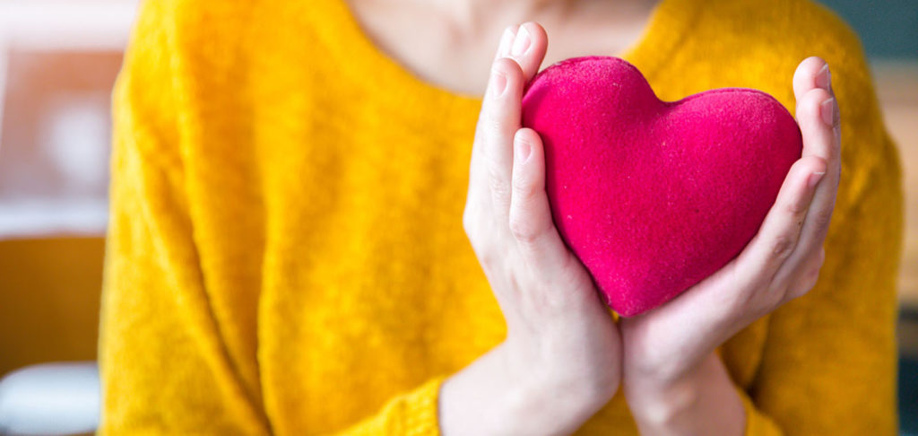 close up of woman hands in yellow sweater holding pink heart.