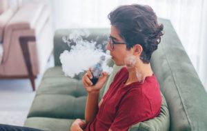 skinny male teenager blowing cotton candy vape smoke