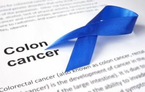 blue ribbon over printed paper with the words colon cancer