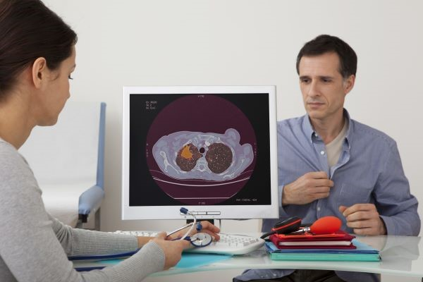 lung image on a pc with a middle aged man in the background